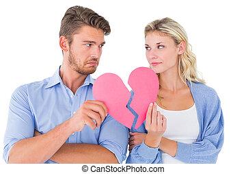 Couple holding two halves of broken heart on white...