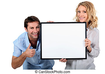 Couple holding up a blank sign