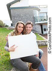 Couple holding whiteboard in front of their house