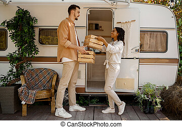 Couple holds provision near rv, camping in trailer