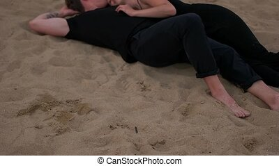 Couple hug lying on the sand