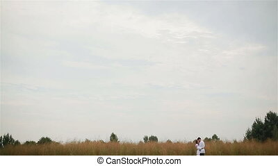 Couple hugging and kissing in field