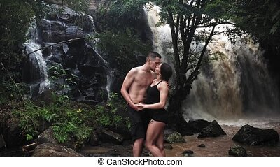 Couple hugging and kissing under a waterfall in a cave. A...