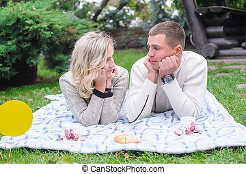 Couple hugging in a park seated in a bench