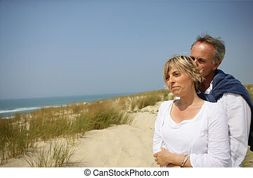 Couple hugging in a sand dune
