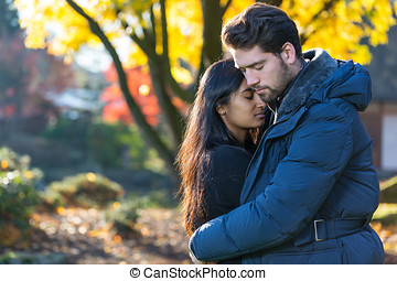 Couple hugging in front of autumn tree