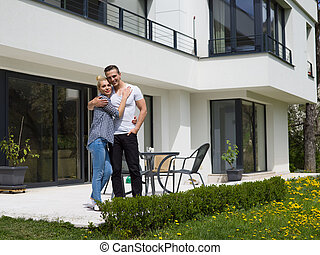 couple hugging in front of new luxury home