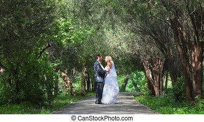 just married couple hugging on a park alley looking at each other's eyes