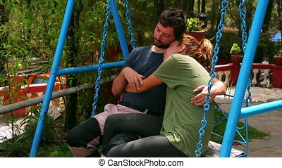 Couple hugging on swing