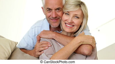 Couple hugging on the couch and smiling