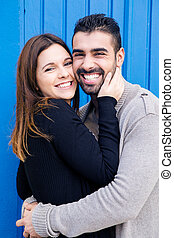 Couple hugging over blue background - Young romantic couple...