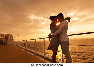 couple hugging with eyes closed at sunset on cruise -...