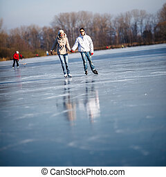 Couple ice skating outdoors on a pond