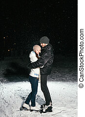 Couple ice skating outdoors on a pond night