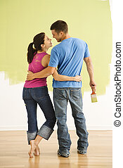 Couple improving home. - Attractive couple standing in front...