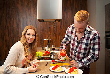 Couple in a kitchen cooking pasta and drinking red wine