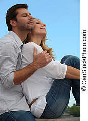 Couple in a loving embrace sitting in the sunshine