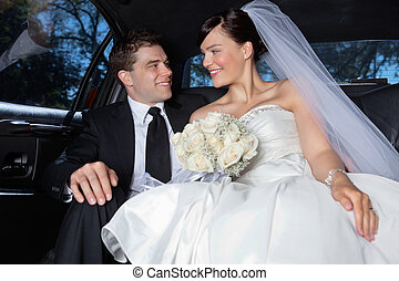 Couple in a luxurious car - Happy newlywed couple in a...