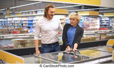 Couple in a supermarket shopping with a shopping cart buying groceries