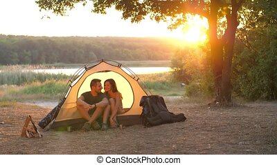 Couple in a tent on nature - Young couple resting in camping...