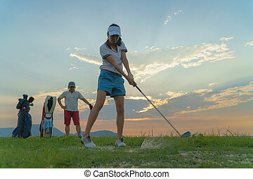 Couple in action of playing golf together.
