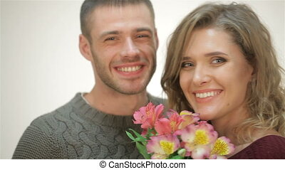 Couple in an embrace holding a bouquet of flowers