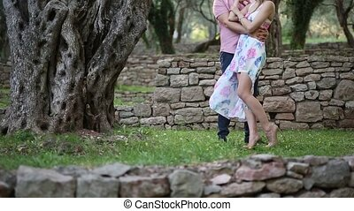 Couple in an olive grove. The newlyweds embrace in the...