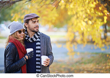 Couple in autumn park - Young people walking in autumn park