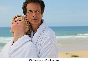 Couple in bathrobes on the beach