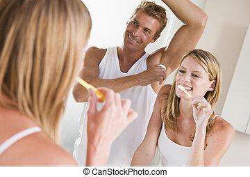 Couple in bathroom brushing teeth and applying deodorant