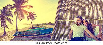 Couple in beach parasol at tropical beach