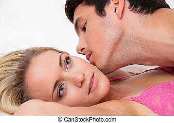 couple in bed during sex and affection. love and e