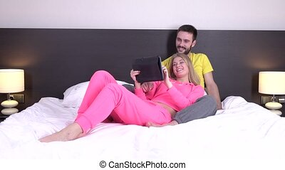 Couple in bed watching movies on computer laptop