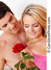 couple in bed with rose. proposal