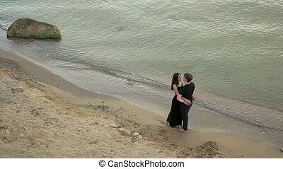 Couple in black clothing embracing by the sea