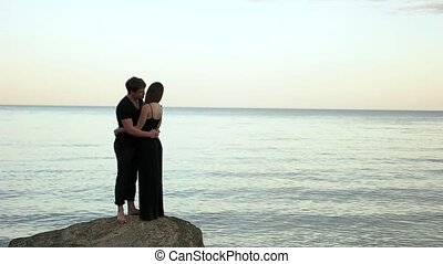 Couple in black clothing embracing on the rock by the sea