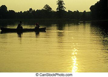 Couple in Canoe - Dusk scene of two figures in a canoe on a...