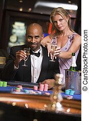 Couple in casino at roulette table holding champagne and smiling (selective focus)