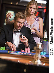 Couple in casino playing roulette and smiling (selective focus)