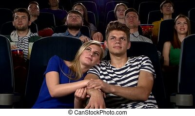 Couple in cinema watching a movie, and kissing