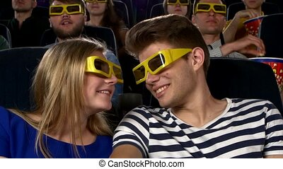 Couple in cinema watching a movie with 3D glasses. Close Up