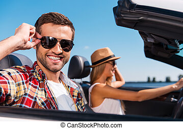 Couple in convertible. Beautiful young couple enjoying road trip in their convertible while handsome man adjusting his sunglasses and smiling