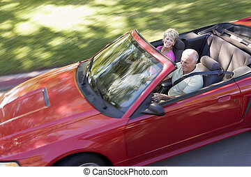 Couple in convertible car smiling