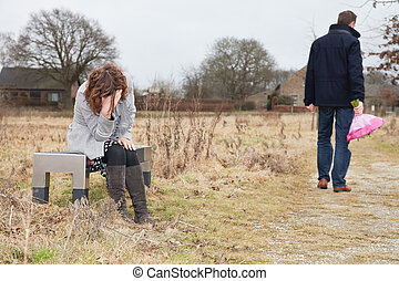 Unhappy man walking away from woman after a huge quarell