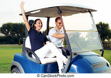 Couple in driving buggy on golf course