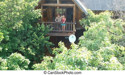 Couple in Forest Resort House with Woman Waving at Rising Drone