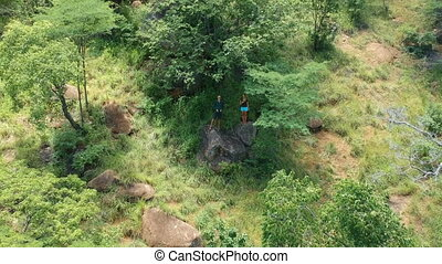 Couple in Forested Slope with Woman Waving at Rising Drone Camera