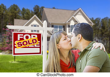Couple in Front of Real Estate Sign and House
