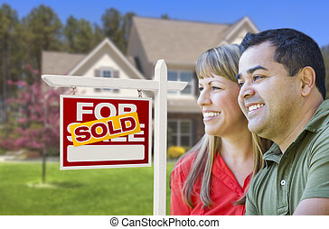 Couple in Front of Sold Real Estate Sign and House