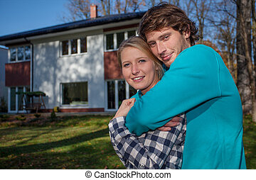 Couple in front of the new house